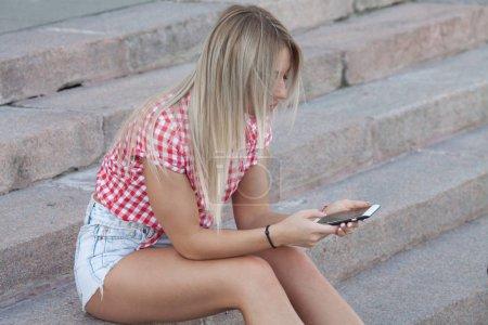 Photo pour Bavardant avec des amis. Belle jeune femme à l'aide de son téléphone intelligent et souriant tout en étant assis sur les escaliers en plein air - image libre de droit