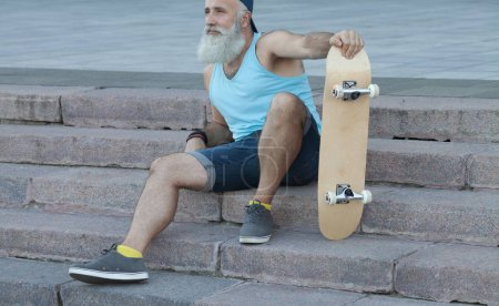 Photo for Trendy old bearded man  with skateboard in town, relaxing on stairs - Royalty Free Image