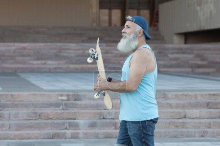 Happy Brodaty starzec. Koncepcja zadowolenie z życia. Portret pozytywny człowiek siwy z deskorolka. Koncepcja zwycięzca.