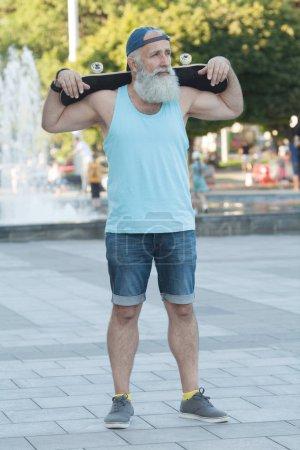 Photo pour Vieil homme énergique qui aime faire du skateboard - image libre de droit