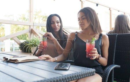 Photo pour Couple femmes ont des expressions postive, s'asseoir près de l'autre à la cafétéria, sourire joyeusement, profitez de délicieux desserts à la cafétéria en plein air. Lesbiennes multiethniques communiquent entre eux. Concept de l'amour. - image libre de droit