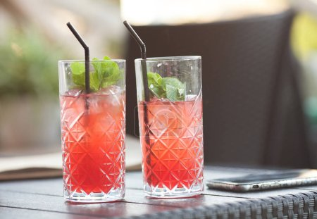 Photo for Alcoholic drink with raspberry liqueur and ice. Two glasses of refreshing cocktail with berries and mint on a blurred background, copy space - Royalty Free Image