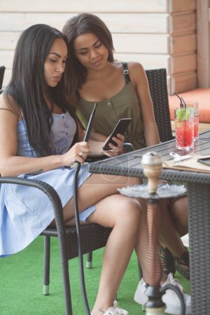 Photo for Multiethnic women read notification with positive news on mobile phone, spend free time in terrace cafe, embrace each other, have happy expressions. Two diveristy females choose something in internet - Royalty Free Image