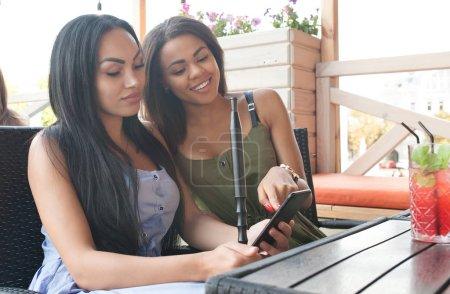 Foto de Mujeres multiétnicas leer notificación con noticias positivas en el teléfono móvil, pasan tiempo libre en la terraza cafetería, abrazan, expresiones felices. Dos hembras de diversidad elegir algo en internet - Imagen libre de derechos