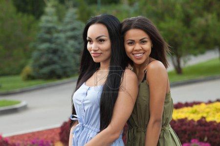Foto de Retrato al aire libre de dos amigas multiétnicas. Chicas en trajes casuales dando un paseo en la ciudad, divirtiéndose y abrazarse, copia espacio. Estilo de vida urbano, concepto de amistad - Imagen libre de derechos