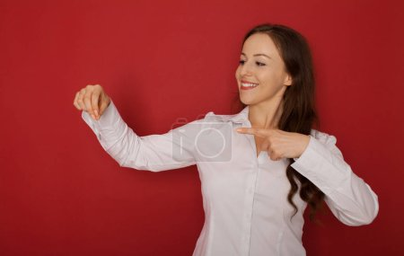 Photo pour Portrait d'une jeune femme stupéfaite pointer du doigt loin au fond isolé sur fond rouge - image libre de droit