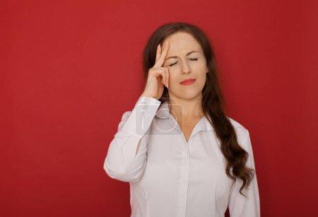 Photo pour Une femme d'affaires avec un mal de tête tenant tête, isolé sur un fond rouge - image libre de droit