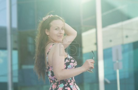 Photo for Portrait of happy smiling woman standing on the square on sunny summer or spring day outside, cute smiling woman looking at you, attractive young girl enjoying summer - Royalty Free Image