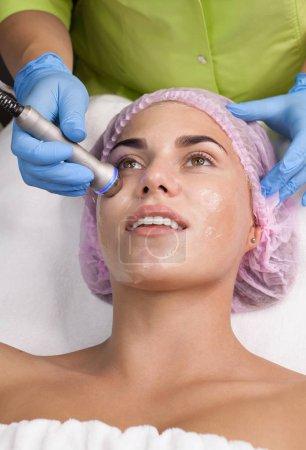 Photo pour Belle femme à obtenir la levée de la radiofréquence sur son visage. Esthéticienne professionnelle faisant soin du visage anti-rides. Concept de soins de la peau et la correction de la texture de la peau. - image libre de droit