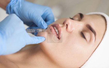 Photo for The cosmetologist makes injections of botulinum toxin in the lips of the patient. Cosmetology skin care. - Royalty Free Image