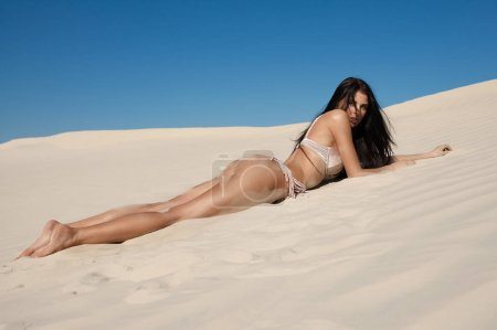 Photo for Amazing girl with sexy body is engaged in fitness on the white sand beach. Young women in swimsuit sunbathing on a summer vacation abroad. Charming model on a desert island. - Royalty Free Image