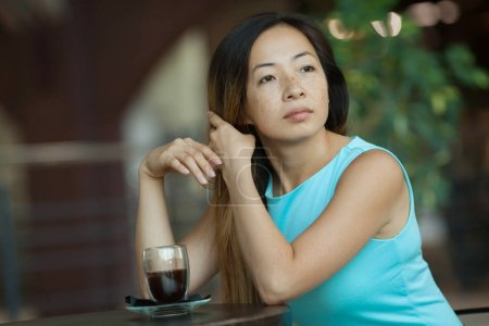 Photo for Thoughtful young woman looking away while sitting in cafe - Royalty Free Image