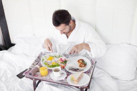 Photo pour Heureux célibataire petit déjeuner au lit - image libre de droit