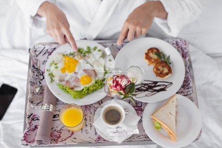 Photo for Happy single man eating breakfast in bed - Royalty Free Image