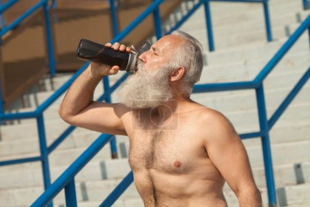 Photo for Little break. Thirsty senior man in sportswear relax after training outdoor, drinking water from bottle. Active lifestyle and healthcare, copy space. Senior man with naked torso. - Royalty Free Image