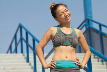 Photo for Fitness sport girl fashion sportswear doing yoga fitness exercise on stairs. Fit young asian woman doing training workout in morning. Young happy asian woman stretching at park after running workout. - Royalty Free Image