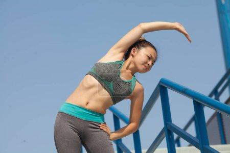 Photo pour Fitness sport fille fashion sportswear faire des exercices de remise en forme d'yoga dans les escaliers. Fit la jeune femme asiatique faisant d'entraînement dans la matinée. Jeune femme asiatique heureuse qui s'étend dans le parc après l'exécution d'entraînement. - image libre de droit