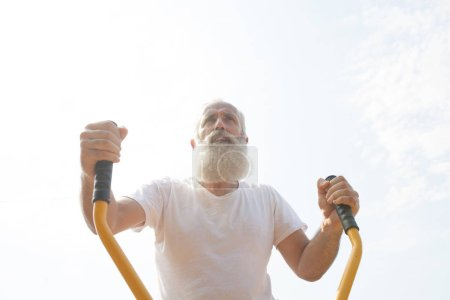 Photo for Old man making exercises on outdoor gym against green summer park as a background. - Royalty Free Image