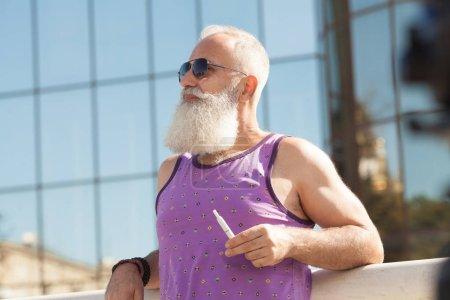 Photo pour Barbu de homme senior vaping - image libre de droit