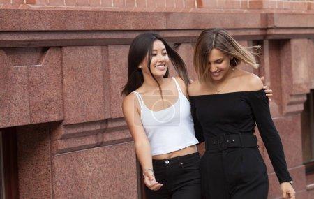 Foto de Happy meeting of two friends hugging in the street - Imagen libre de derechos