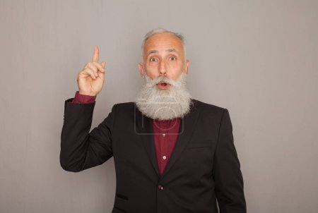 Photo for Excited old bearded businessman having an idea and pointing finger up at copy space - Royalty Free Image