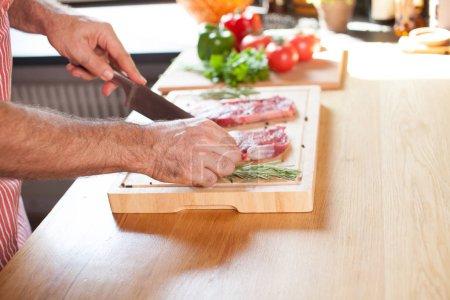 Photo pour Bifteck de filet mignon de bœuf cru sur une planche à découper avec romarin poivre sel fourchette et couteau. - image libre de droit