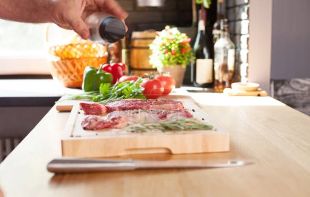 Photo for Extreme close-up of seasoned meat. Man peppering steaks with grains of pepper. Meat surrounded with vegetables and rosemary lying on the table - Royalty Free Image