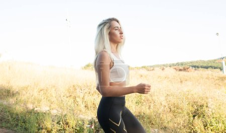 Photo for Woman sport running on sunny hill for fitness - Royalty Free Image