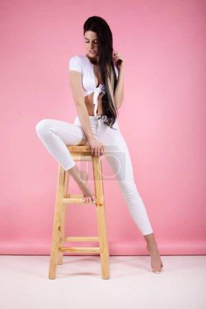 Photo pour Verticale pleine longueur de jeune femme dans des vêtements blancs restant d'isolement sur un fond rose. Regardant l'appareil-photo. - image libre de droit