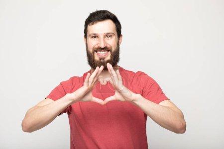 Photo pour Verticale de plan rapproché de son il il joli beau bel bel homme barbu positif gai utilisant le t-shirt vérifié affichant le petit ami de forme de coeur 14 février d'isolement au-dessus du fond pastel beige - image libre de droit