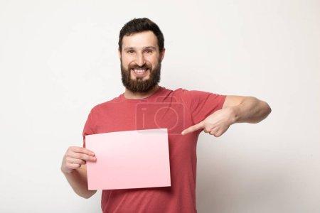 Photo pour Jeune homme barbu avec la bannière rose blanche. Homme de sourire retenant la feuille de publicité, espace de copie, isolé - image libre de droit
