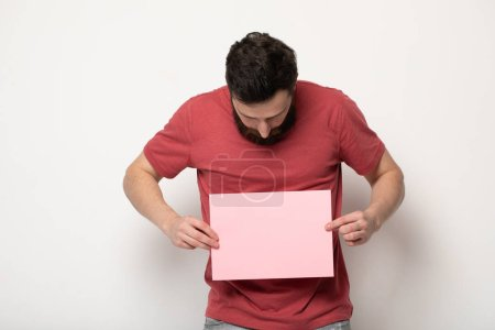 Photo for Young bearded man with blank pink banner. Smiling man holding advertising sheet, copy space, isolated - Royalty Free Image