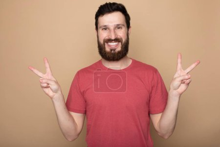Photo for Image of a handsome happy excited bearded man posing isolated over beige wall background make winner gesture. - Royalty Free Image