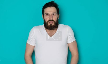 Photo for Utter indignation. young shoked bearded man dumbstruck from someones impertinence or impudence. people emotional reaction concept. portrait of a casual hipster guy on blue background. - Royalty Free Image