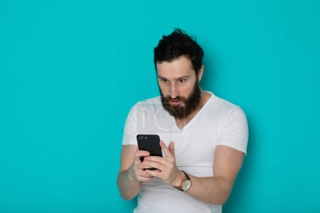 Photo for Portrait of a surprised casual man looking at mobile phone isolated over blue background - Royalty Free Image