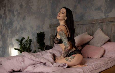 Photo pour Sensuelle belle tatoua femme parfait corps mince qui pose en lingerie sexy portant de chambre à coucher. - image libre de droit