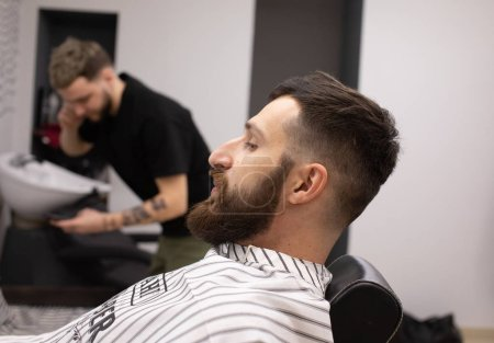 Photo for Client during beard and moustache grooming in barber shop - Royalty Free Image