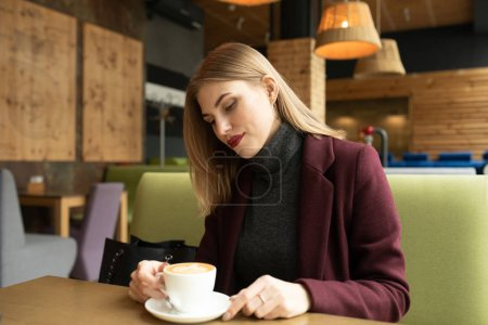 Photo for Beautiful smiling woman drinking coffee at cafe. Portrait of blonde woman in a cafeteria drinking hot cappuccino and looking at camera. Pretty woman with cup of coffee. - Royalty Free Image