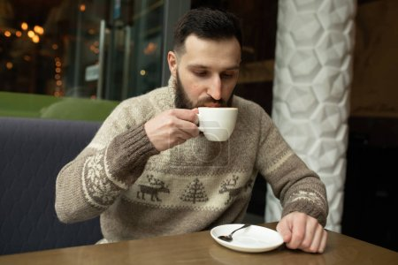 Photo for Handsome young man drinking coffee at the coffeehouse - Royalty Free Image