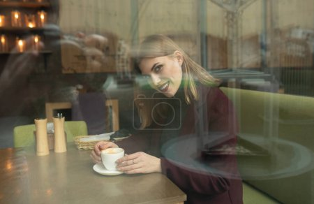 Photo for Girl holds a coffee cup at local coffee shop, concept photo through window for city effect with reflection - Royalty Free Image