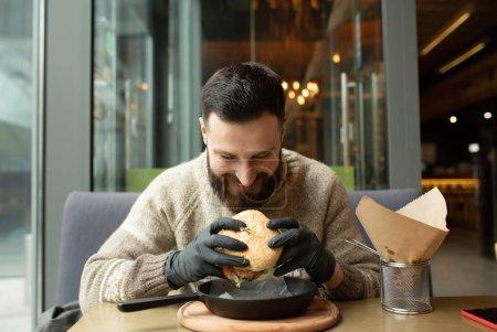 Photo pour Hamburger heureux homme manger au restaurant - image libre de droit