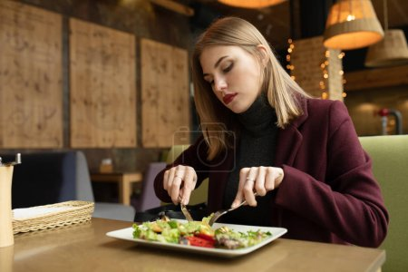 Photo for Blonde woman eating green healthy tasty eco salad on city cafe - Royalty Free Image