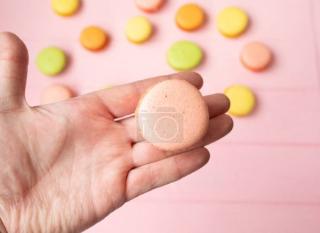 Photo for Hand holding Sweet and colourfull french macaroons or macaron on pink background - Royalty Free Image