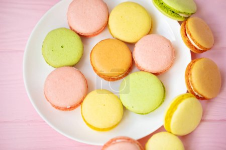 Photo for Colorful French or Italian macarons stack on white plate put on pink wood table with copy space for background. Dessert for served with afternoon tea or coffee break. - Royalty Free Image