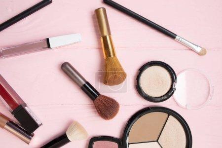 Photo pour Pinceau de maquillage et cosmétiques décoratifs sur fond rose pastel avec espace vide. - image libre de droit