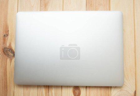 Photo pour Fermé pour ordinateur portable sur un fond en bois - image libre de droit
