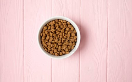 Photo for Cat food in bowl on pink wooden background - Royalty Free Image