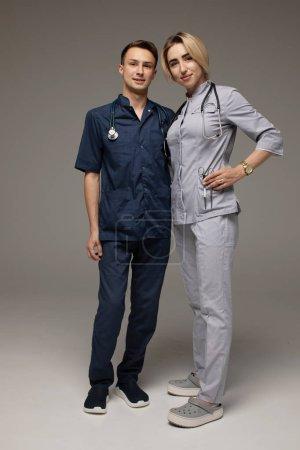 Photo pour Heureux travailleurs médicaux. Portrait de deux médecins en manteaux blancs sur fond gris - image libre de droit