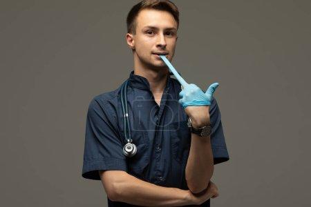 Photo pour Jeune homme médecin portant des gants médicaux se préparant à l'examen souriant à la caméra gaiement, confiance, médecine et concept de profession de la santé - image libre de droit