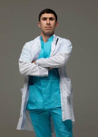 Photo pour Attrayant sérieux jeune médecin homme posant sur un fond gris. - image libre de droit